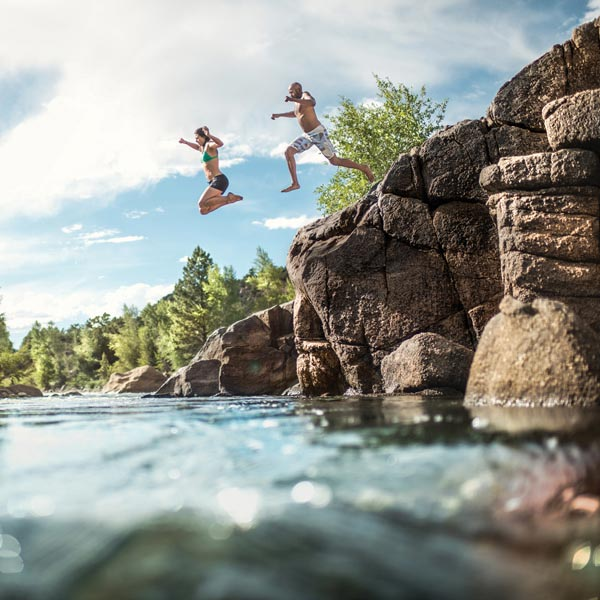 "Swimmers leap from a rock face to the river below, with the words ""we no longer need to seek permission."""