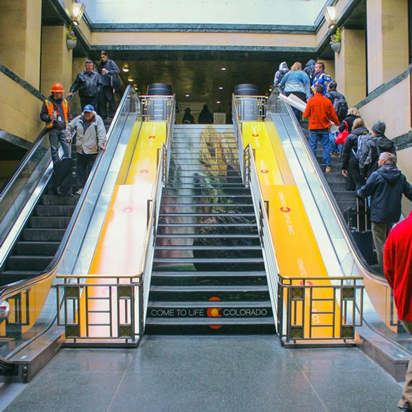 Busy escalators and a 'Come to Life Colorado' staircase wrap.