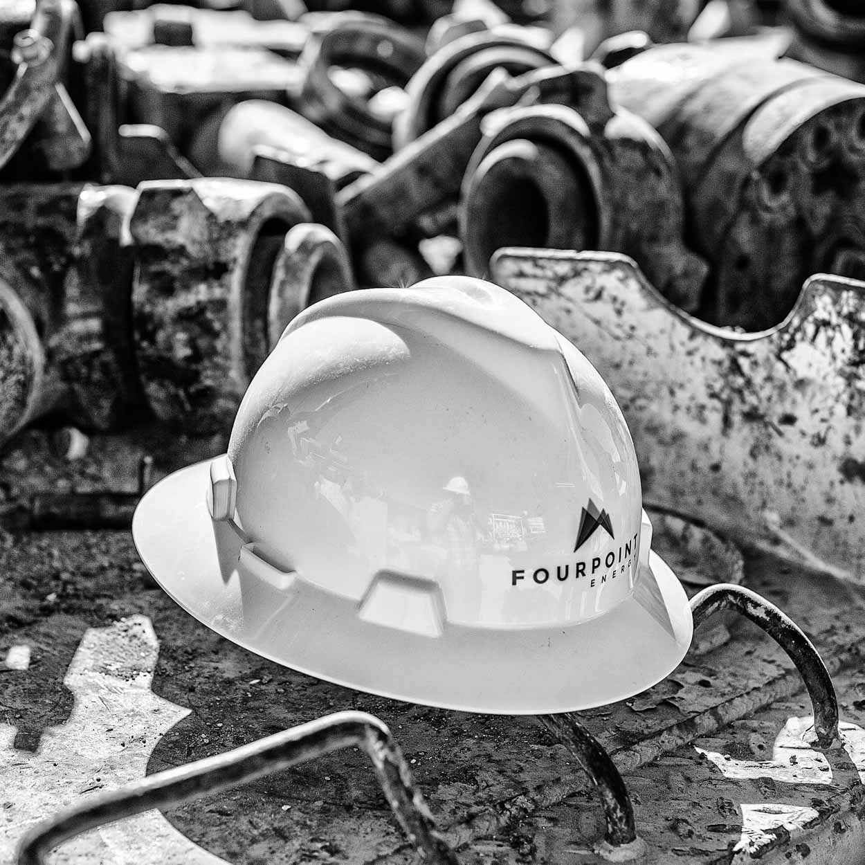 Black and white photograph of a branded hardhat sitting on top of dirty pipe fittings.