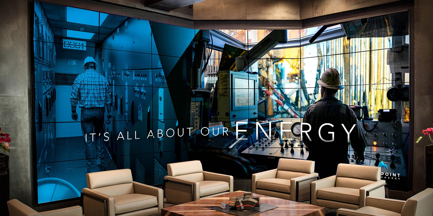 "Photograph of the Fourpoint office featuring a large-format video wall displaying images of oil rig workers and the words, ""It's all about our energy."""