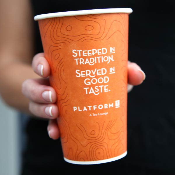 Hands holding branded to-go coffee cups.