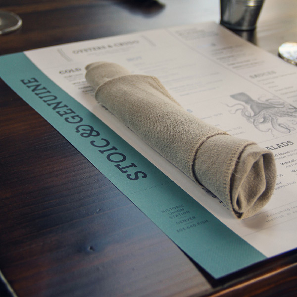A beautifully design menu sits on a wooden restaurant table.