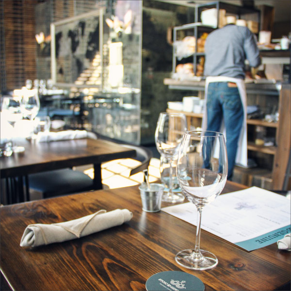 Interior shot of the Stoic & Genuine restaurant featuring rustic tables, wine glasses and cloth napkins.