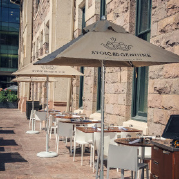 Exterior photograph of the sidewalk patio with branded table canopies.