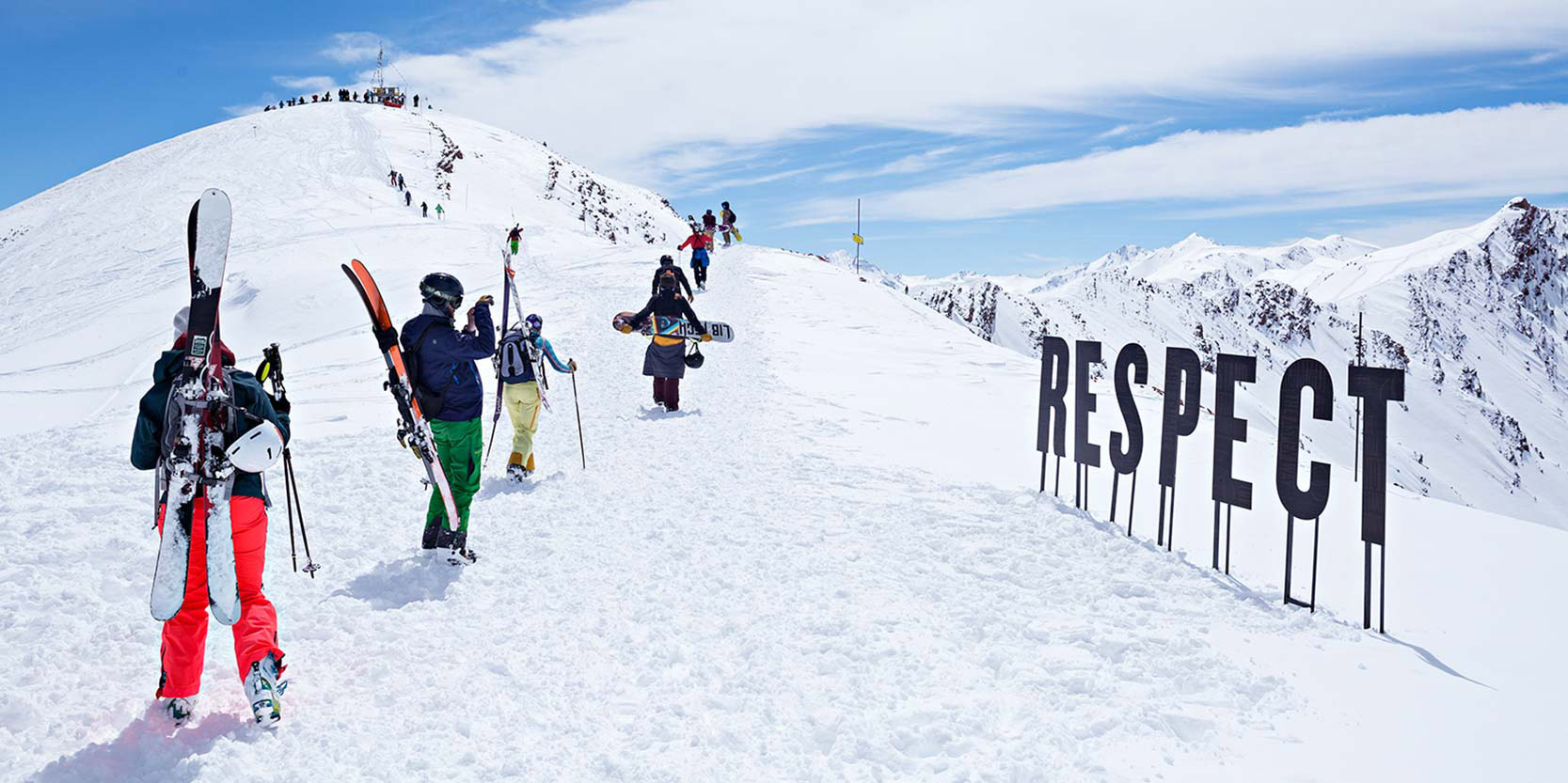 "Print advertisement featuring skiers climbing a summit with a sign that reads, ""Respect."""