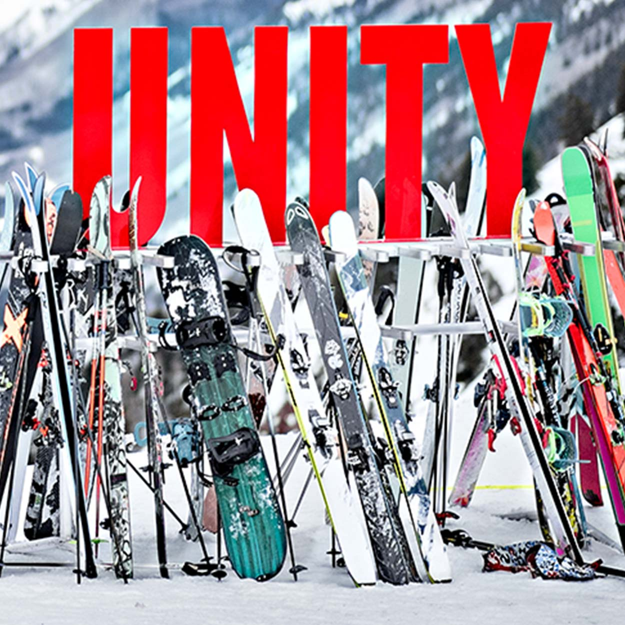 "Many skis and snowboards stacked against a stand, with the word ""Unity."" and blurry mountains in the background."