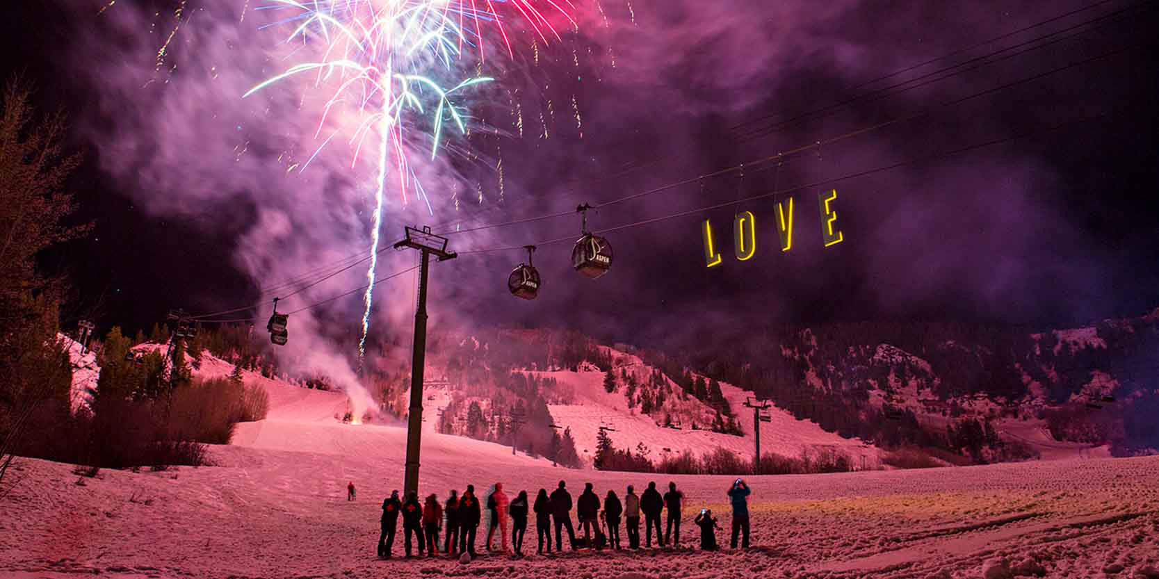 Many skiers at the bottom of the slope at night. Fireworks illuminate the sky and a sculpture hangs from the ski lift and says LOVE.
