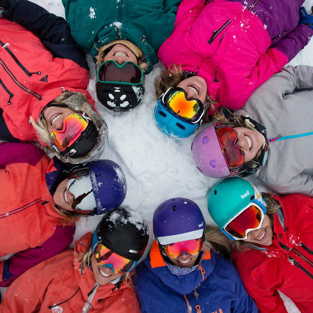 Smiling skiers lying in a circle on the snowy ground.