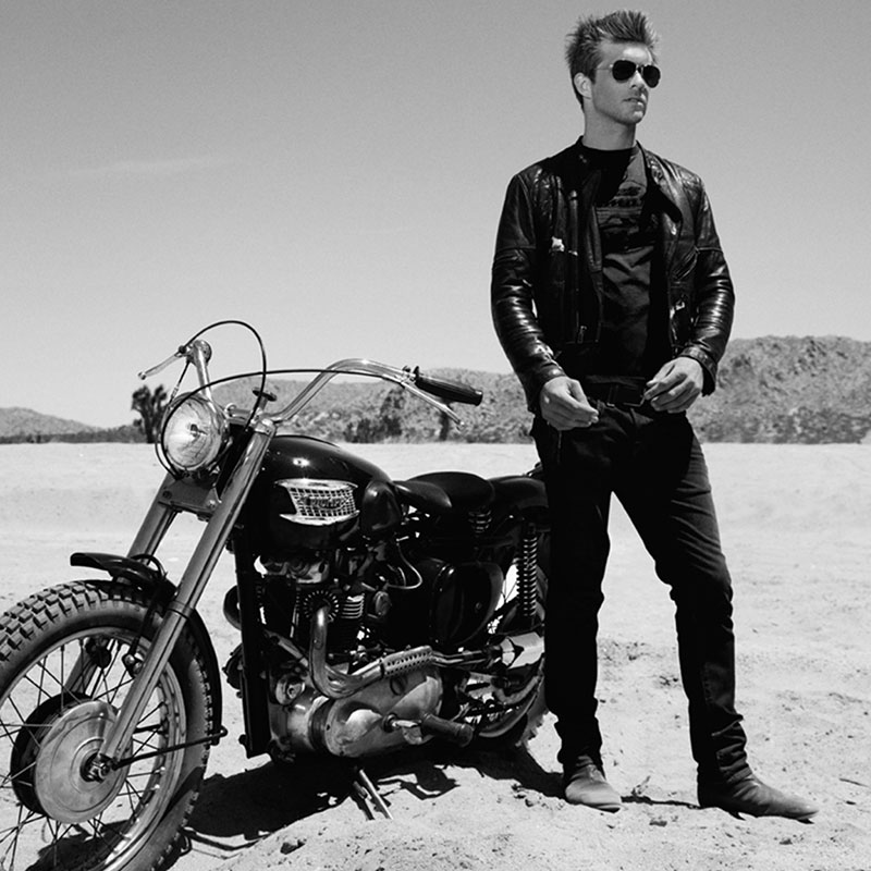 Black and white photograph of a desert scene featuring a man with great hair, a leather jacket and a Triumph motorcycle.