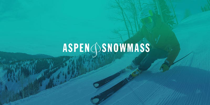 Stylized medium shot of a skier racing down the slope, overlaid with the Aspen Snowmass logo.