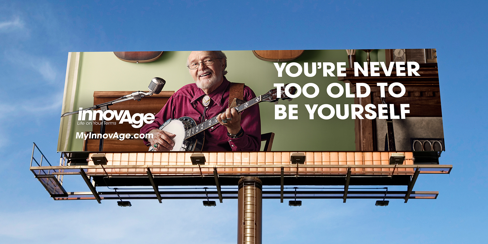 "Outdoor billboard showing an elderly man playing banjo in his living room, with the words ""You're never too old to be yourself."""