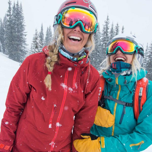 Two women in full ski gear, laughing as the snow falls.