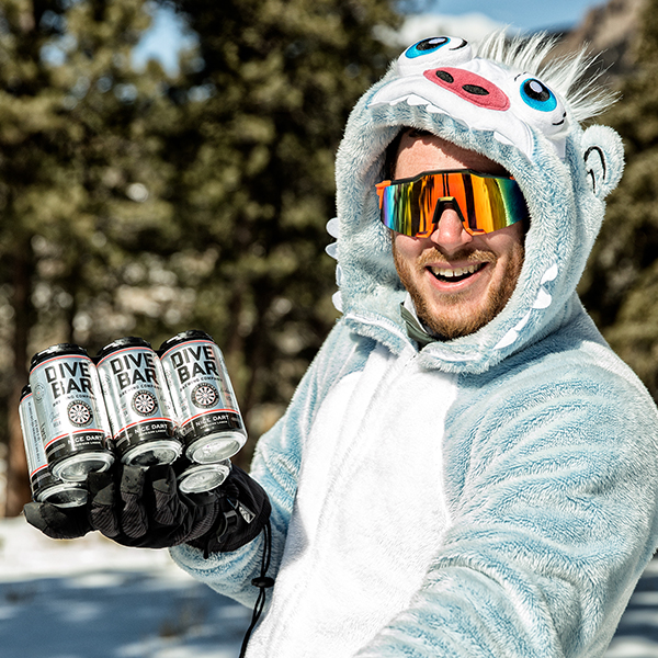 Smiling man in a furry costume, wearing ski glasses and holding a six-pack of Dive Bar Beer.