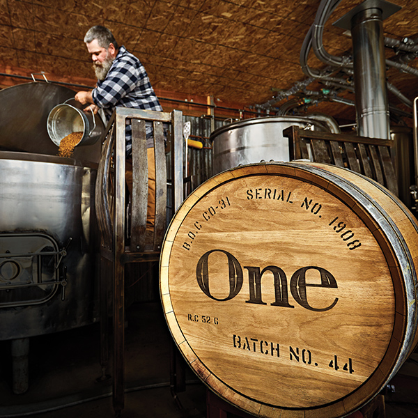 "Brewmaster pouring hops into a large metal vat, and the word ""One"" engraved into a wooden barrel."