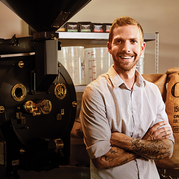 "Smiling man stands in front of a large, black coffee-bean roaster. The word ""One"" is engraved on a burlap sack of fair-trade coffee beans."