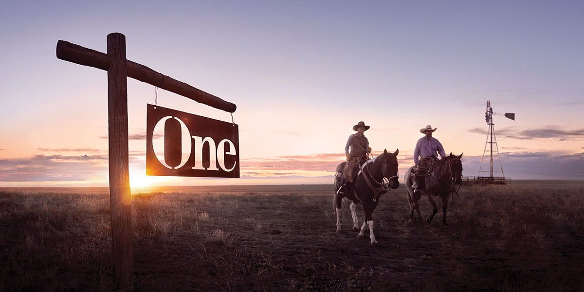 "Two men on horseback ride past an old wooded sign that reads, ""One."""