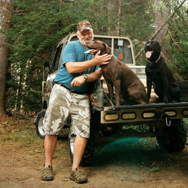 Man on hunting trip with dog in truck