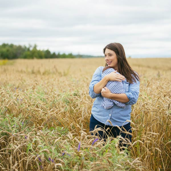 woman holding newborn baby in field