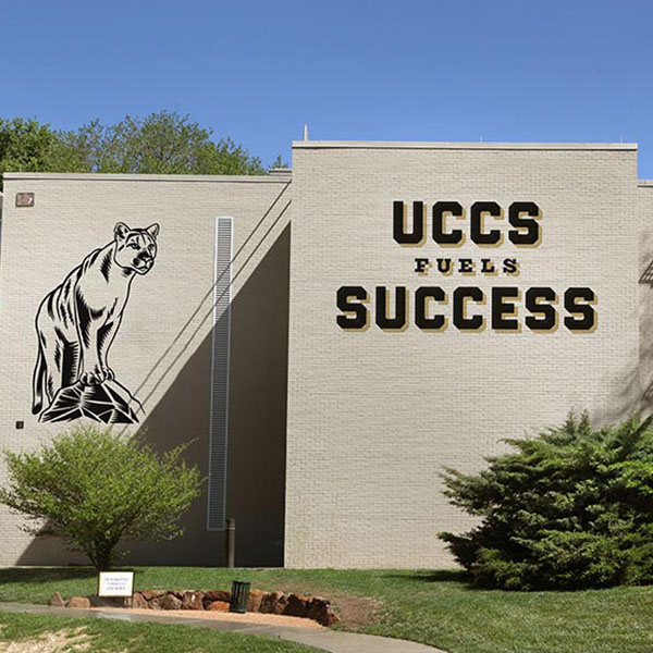 "Mural on a UCCS dorm featuring a mountain lion and the words ""UCCS Fuels Success."""