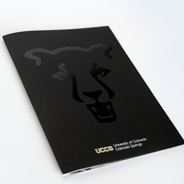 A UCCS pamphlet, fully black with a glossy outline of an iconized lion.
