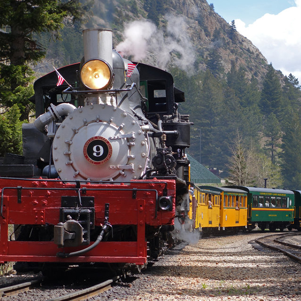Photograph of a colorful, old-timey train surging through the mountains.