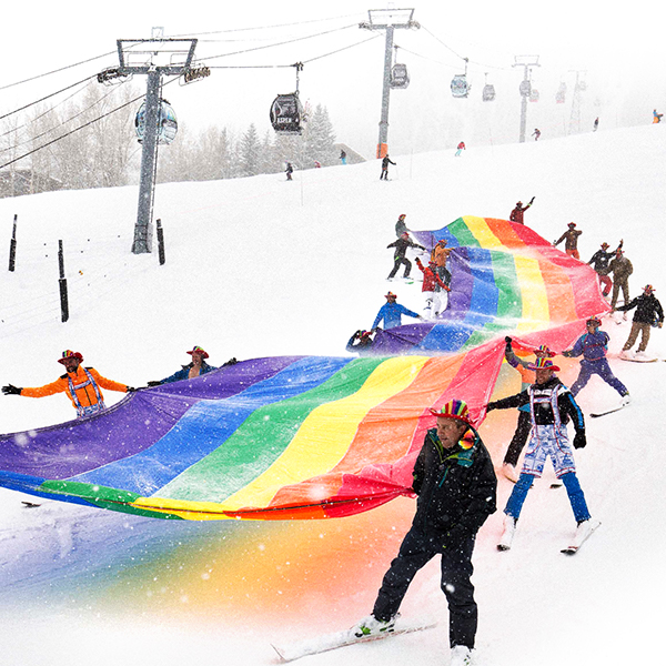 """Give a Flake"" print advertisement featuring skiers collaboratively holding a large rainbow flag as they ski down a slope, and the words ""If your favorite color is all of them."""