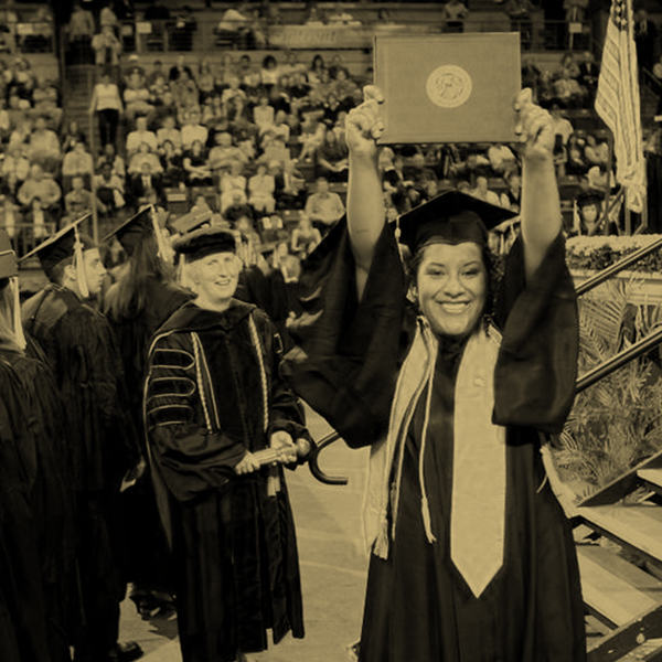 Stylized photograph of a graduating student holding up their diploma.