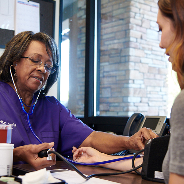 woman in purple vitalant scrubs checking patient's blood pressure