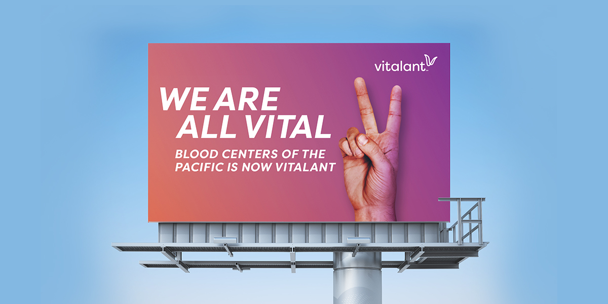 photo of billboard with we are vital messaging and hand with peace sign
