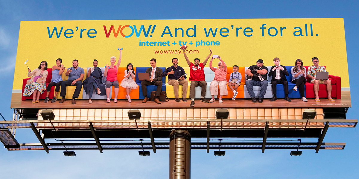 "Incredibly long multi-colored couch with a diverse set of characters, and the words ""We're Wow! And we're for all."""