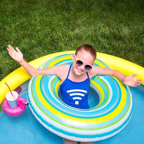 Smiling child in a kiddie pool while a parent sits nearby using a laptop. Both have a Wifi symbol on their shirt.