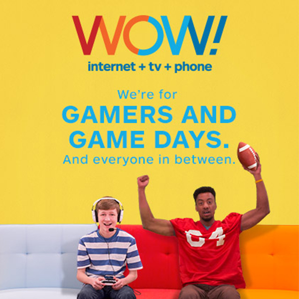 "Out-of-home sidewalk display with two people, one is playing a video game and the other wears a football jersey. The words read, ""We're for gamers and game days. And everyone in between."""