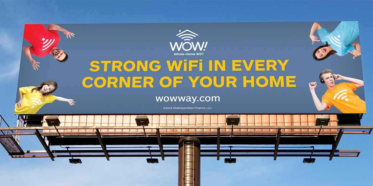 "Outdoor Billboard with four people wearing shirts with Wifi symbols, and the words ""Strong Wifi in every corner of your home."""
