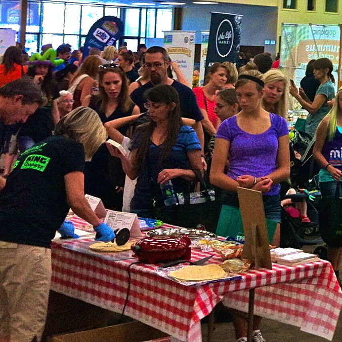 Photo of people trying gluten-free goodies at the fair.